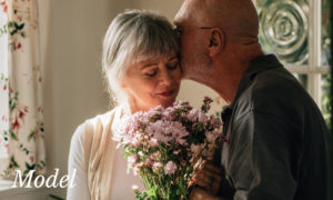 Mature Couple Exchanging Flowers and Embracing